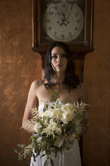Bride holding bouquet of flowers under grandfather clock