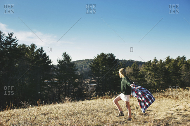 Caucasian woman playing with scarf on rural hilltop