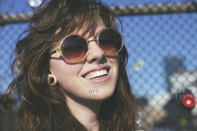 Caucasian woman wearing sunglasses at fence