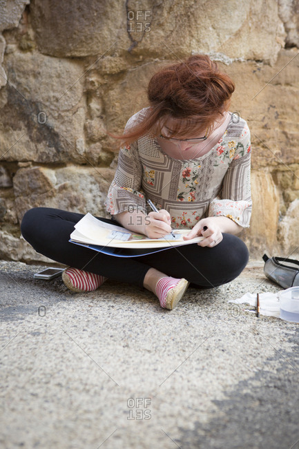 Caucasian girl drawing on concrete ground