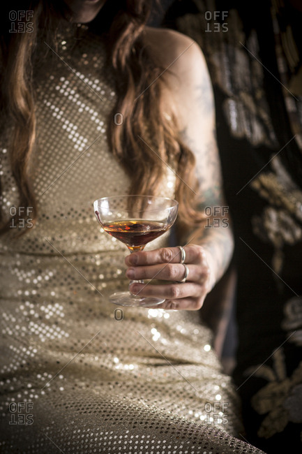 Caucasian woman in evening gown drinking cocktail
