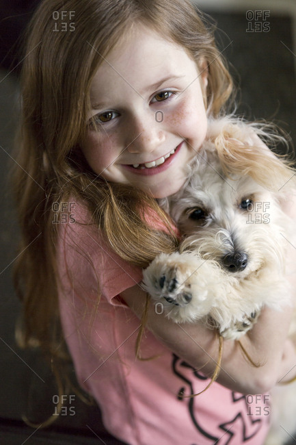 Close up of Caucasian girl hugging puppy