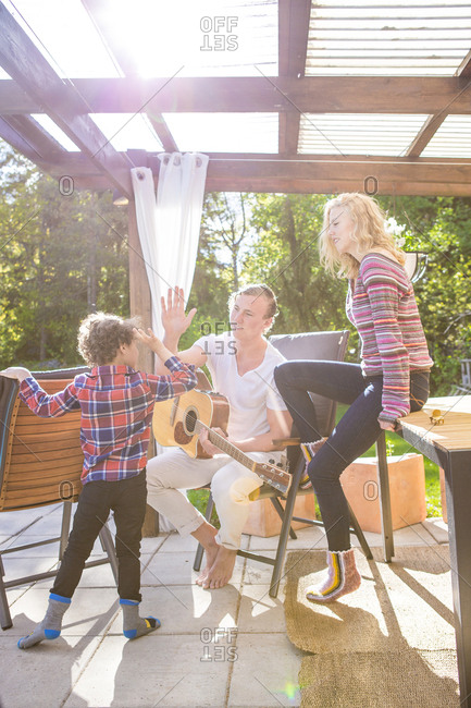 Father and son high-fiving on backyard patio