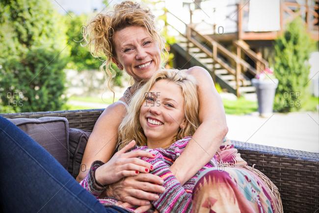 Mother and daughter hugging on backyard sofa