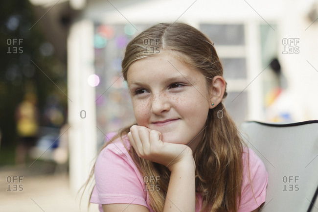 Caucasian girl resting chin in hand