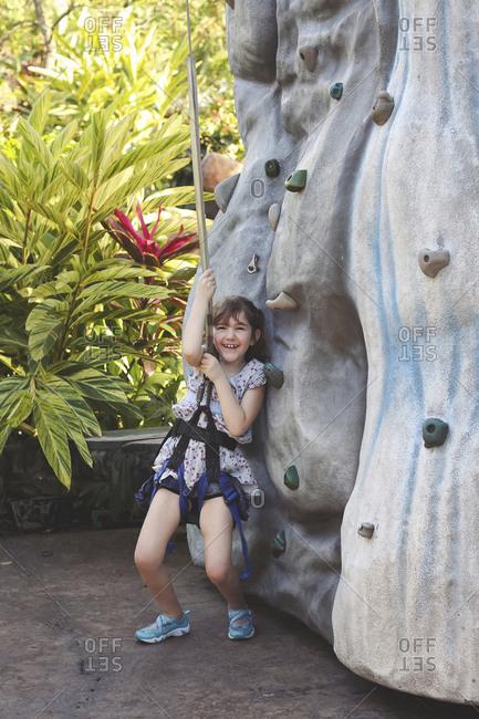 Caucasian girl climbing rock wall in harness