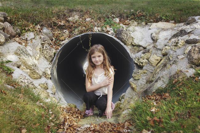 Caucasian girl climbing in storm drain tunnel