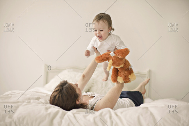 Caucasian mother playing with baby on bed
