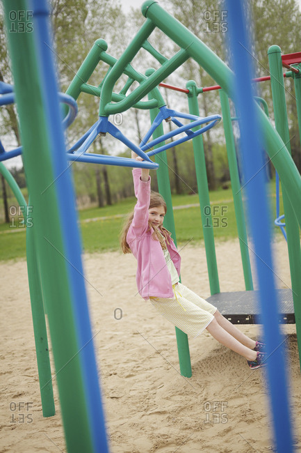 Caucasian girl hanging from structure in playground