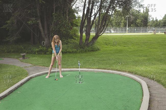 Caucasian girl playing miniature golf