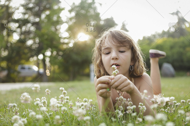 Caucasian girl playing with flowers in backyard