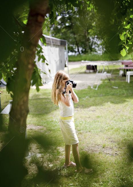 Caucasian girl photographing in backyard
