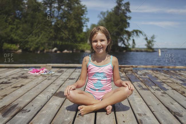 Caucasian girl sitting on wooden dock over lake