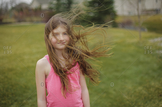 Hair of Caucasian girl blowing in wind in backyard
