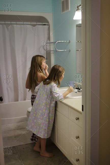 Caucasian sisters brushing teeth in bathroom