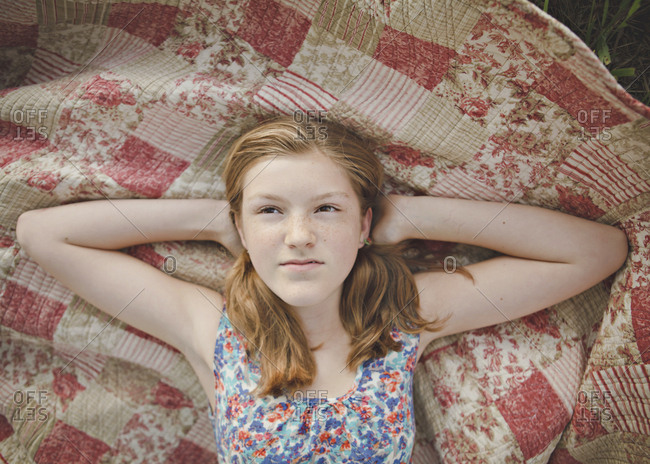 Caucasian girl laying on blanket