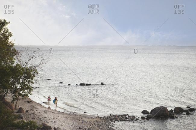 Caucasian girls standing on remote beach