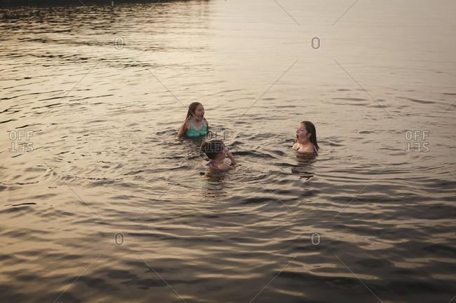 Caucasian girls swimming in lake
