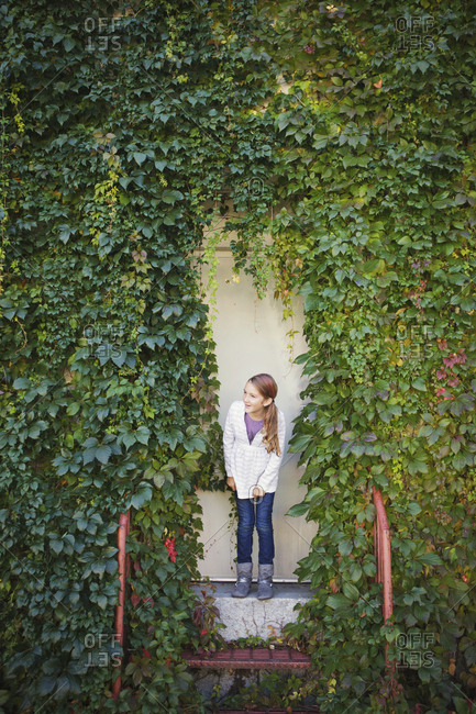 Caucasian girl standing at ivy wall