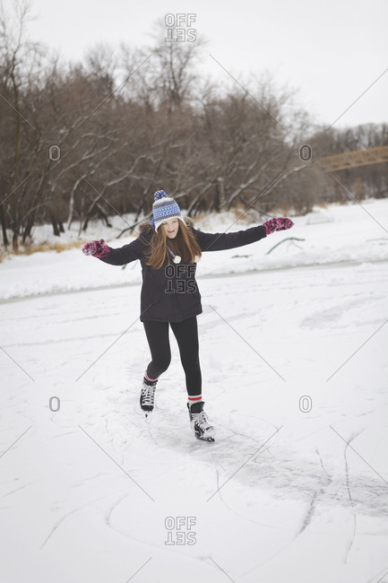 Caucasian teenage girl ice skating on frozen lake