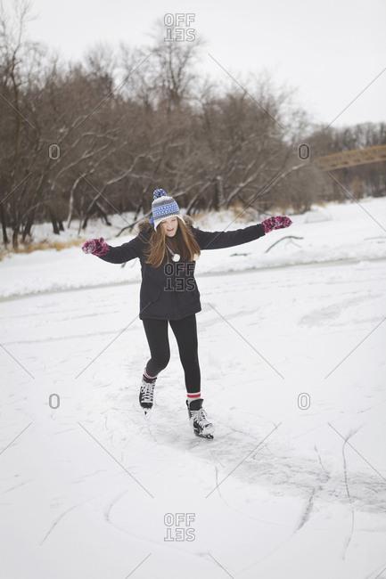 Caucasian teenage girl ice skating on frozen lake