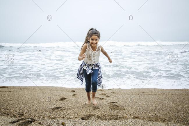 Hispanic girl walking barefoot on beach