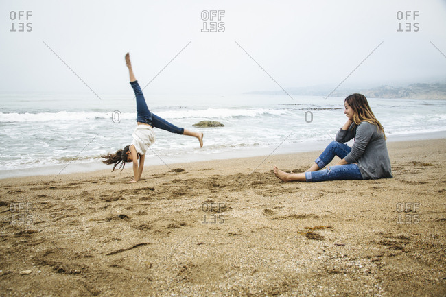 Hispanic mother and daughter playing on beach