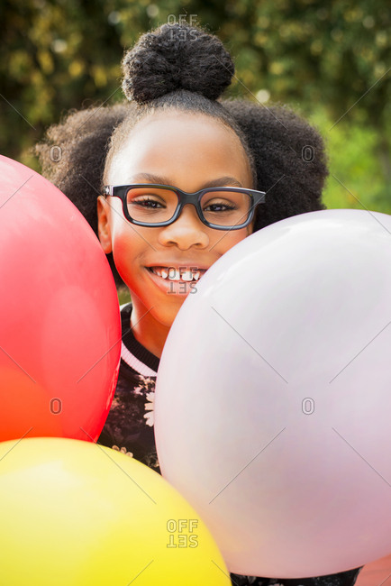 Black girl holding bunch of balloons
