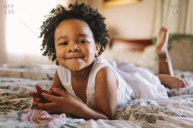 Smiling toddler girl playing on bed