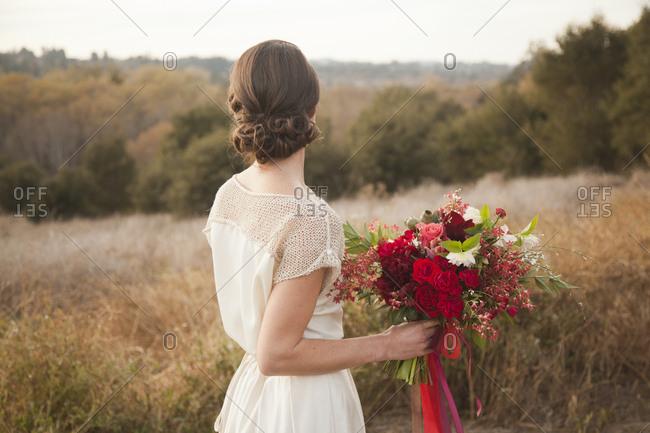 Bride holding bouquet on rural hilltop