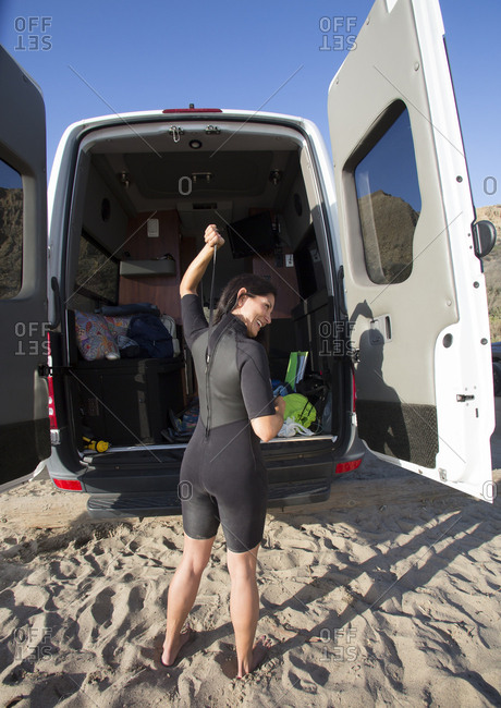 Hispanic surfer zipping wetsuit on beach