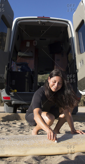 Hispanic surfer waxing her surfboard on beach