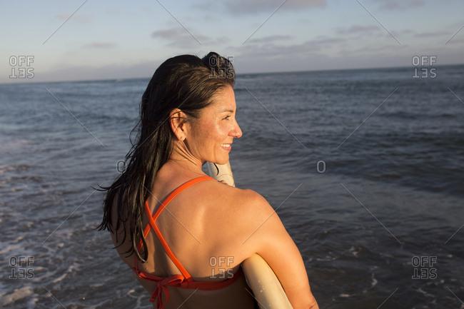 Hispanic woman holding surfboard in ocean