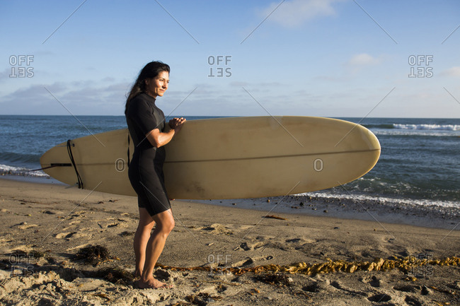 Hispanic surfer carrying surfboard on beach