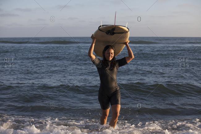 Hispanic surfer carrying surfboard in ocean