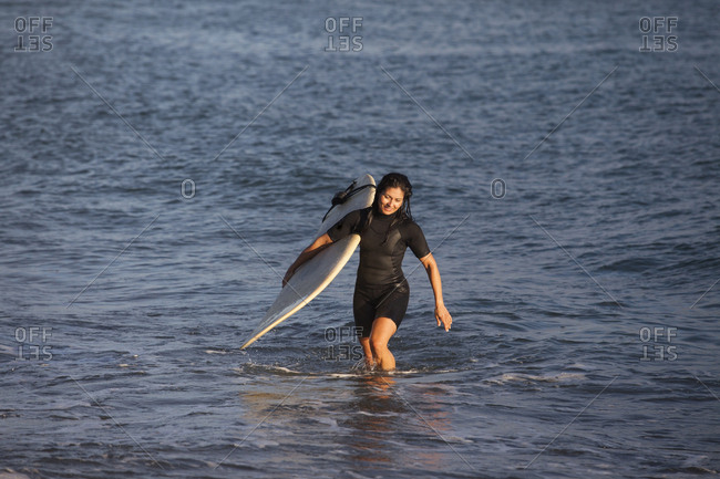 Hispanic surfer carrying surfboard in ocean