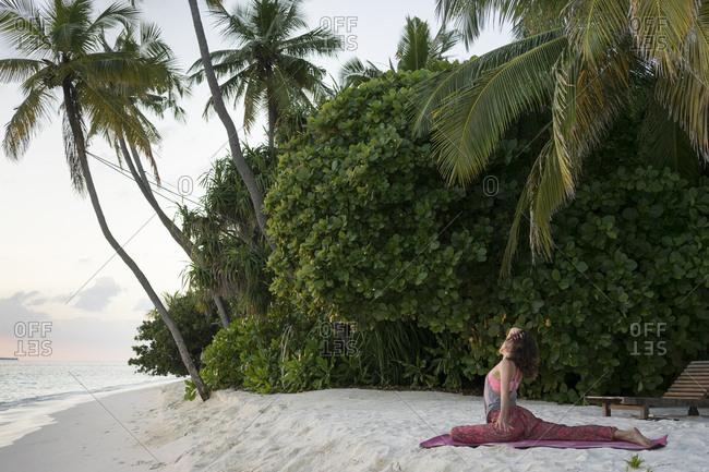 Caucasian woman practicing yoga on tropical beach