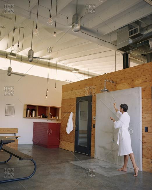 Woman preparing open shower in modern living space