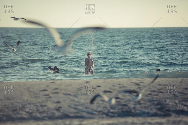 Seagulls flying near Caucasian teenage girl standing in ocean