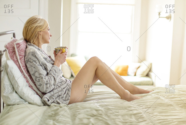 Caucasian woman drinking cup of coffee in bed