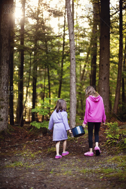 Caucasian girls carrying pot of water in forest