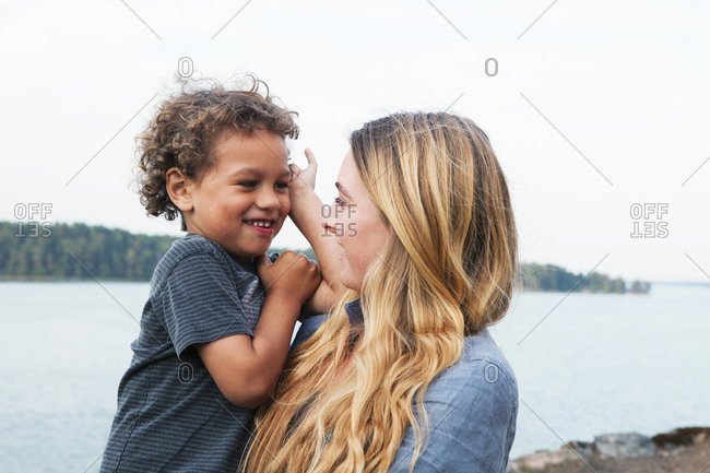 Mother holding son at rural lake