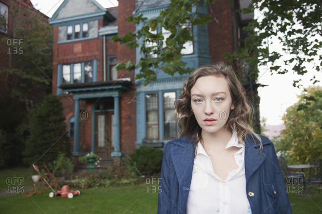 Serious woman standing in front yard