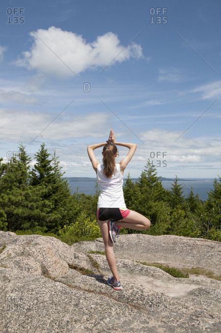 Teenage girl balancing on mountaintop