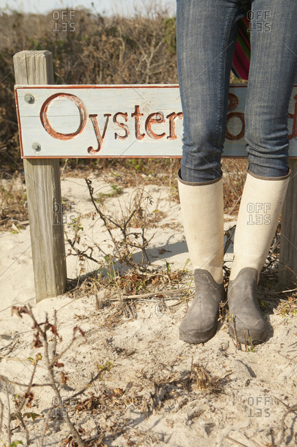 Woman wearing boots near sign on beach