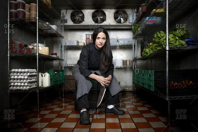 Chef sitting in walk-in refrigerator in restaurant