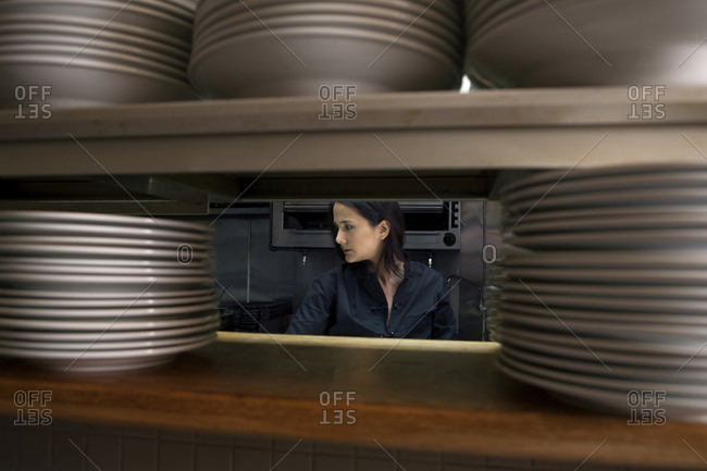 Working chef viewed through stacks of plates in restaurant kitchen