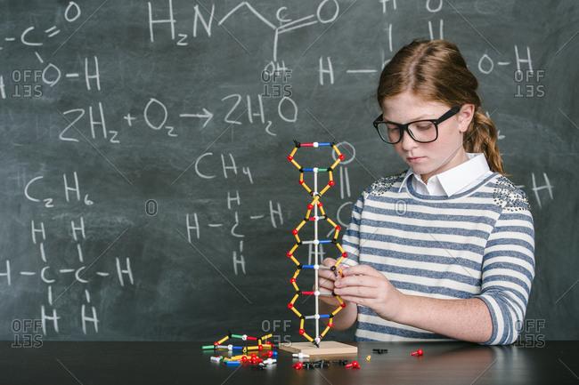 Caucasian student examining molecular model in science class