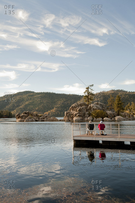 Couple sitting on wooden deck in remote lake