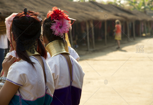 Students wearing traditional jewelry near huts